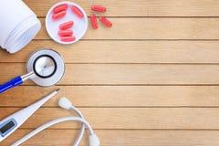 在木医生书桌背景的医疗设备 免版税库存图片