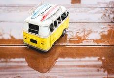 在木头的一个公共汽车玩具在下雨天中 免版税库存图片