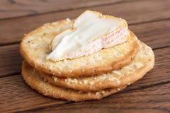 在木头的三个金黄乳酪薄脆饼干 库存图片