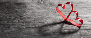 在木头的两丝带心脏 图库摄影