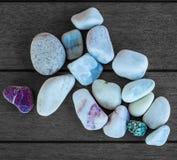在木头的几块小卵石石头构造了塑料背景 免版税库存照片