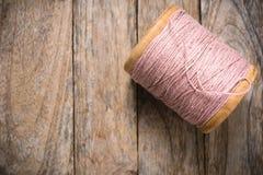 在木头的卷轴桃红色毛线右边 免版税库存图片