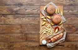 在木头的快餐顶视图 汉堡包、热狗和油炸物 免版税库存图片