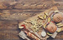 在木头的快餐顶视图 汉堡包、热狗和油炸物 图库摄影