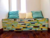 在木头的枕头编结表面上的长凳任意花梢颜色 免版税图库摄影