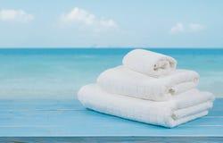在木头的白色海滩毛巾在被弄脏的蓝色海背景 库存照片