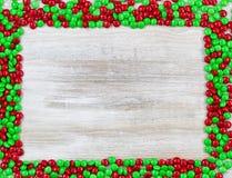 在木头的红色和绿色糖果边界 免版税库存图片