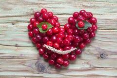 在木头的红色樱桃心脏面带笑容 免版税图库摄影