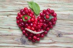 在木头的红色樱桃心脏面带笑容 免版税库存照片