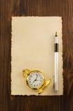 在木头的纸羊皮纸和墨水笔 免版税库存图片
