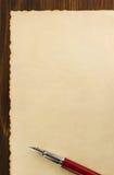 在木头的纸羊皮纸和墨水笔 图库摄影