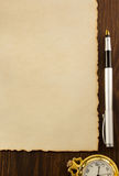 在木头的纸羊皮纸和墨水笔 库存图片