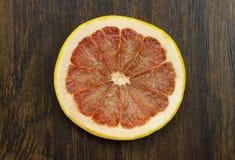 在木头的葡萄柚红色水多的新鲜的热带切的异乎寻常的维生素果子 图库摄影