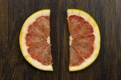 在木头的葡萄柚红色水多的新鲜的热带切的异乎寻常的维生素果子 库存照片