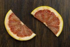 在木头的葡萄柚红色水多的新鲜的热带切的异乎寻常的维生素果子 免版税库存图片