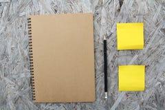 在木头的被回收的纸笔记本 库存照片