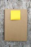 在木头的被回收的纸笔记本 免版税图库摄影