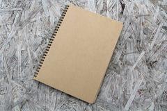 在木头的被回收的纸笔记本 库存图片