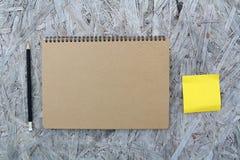 在木头的被回收的纸笔记本 免版税库存图片