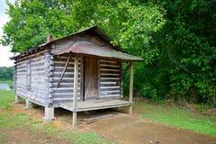 在木头的边缘的原木小屋 库存照片