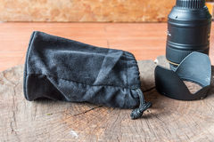 在木头的黑摄象机镜头袋子 免版税库存照片
