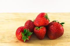 在木头的Strawberrys在白色背景 库存图片