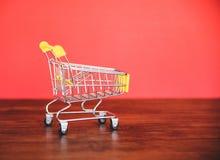 在木/网络购物黑星期五概念的手推车与在红色的黄色手推车 免版税库存照片