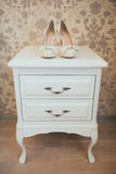 在木洗脸台的白色新娘鞋子 免版税库存照片