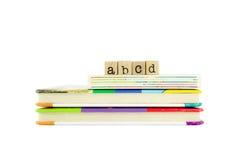 在木头邮票和儿童的板的Abcd词预定 库存图片