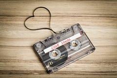 在木backgound的卡型盒式录音机磁带 塑造心脏的影片 库存图片