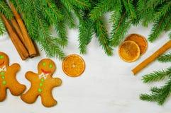 在木backgroun的姜饼人和圣诞树分支 免版税库存图片