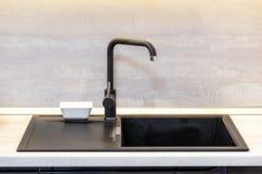 在木worktop的黑陶瓷水槽和明三联式浴缸水嘴在厨房屋子里 库存照片