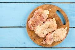 在未加工的小鸡腿上的平的位置用香料准备好烤肉 免版税库存照片