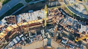 在未完成的大厦,顶视图附近的起重机 建筑用起重机修建站点的一个新的砖房子 股票视频