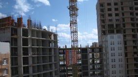 在未完成的居民住房工地工作的起重机举的货物 股票录像
