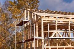 在未完成的房子附近的金属脚手架 生态房子的建筑 房子木制框架建设中 免版税库存照片