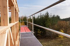 在未完成的房子附近的金属脚手架 生态房子的建筑 房子木制框架建设中 库存图片