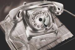 在未来派处理的一个古老银色拨号盘盘电话在立场黑暗背景的桌上 免版税库存照片