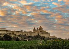在本营附寄的被加强的城市姆迪纳拉巴特中世纪镇史诗日落天空,大小山位于马耳他的中心 免版税库存照片