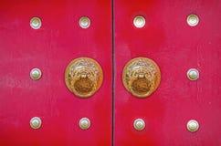 在朱红色的门的龙敲门人 免版税库存照片