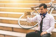 在机动性的商人观看的录影与他的在si的自行车 库存图片