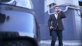 在机动性,此外立场的年轻透视商人谈话与时兴的汽车 股票录像