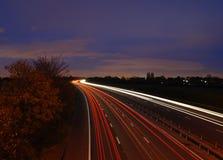 在机动车路的光足迹在黄昏 免版税库存图片