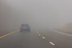 在机动车路的大雾 危险 免版税图库摄影