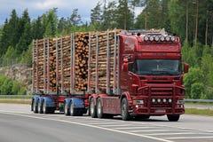 在机动车路的红色斯科讷采伐的卡车黏浆状物质木拖拉 免版税库存图片