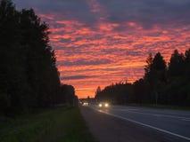 在机动车路路的剧烈的日落 免版税图库摄影