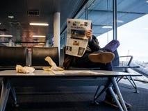 在机场供以人员读书纽约时报杂志报纸 免版税库存图片