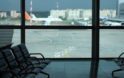 在机场供以座位特写镜头在离开的候诊室 在背景一条窗口和跑道有飞机的 图库摄影