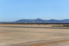 在机场停车处地面的山景 库存照片