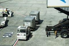 在机场围裙的猛拉移动的货物 库存图片